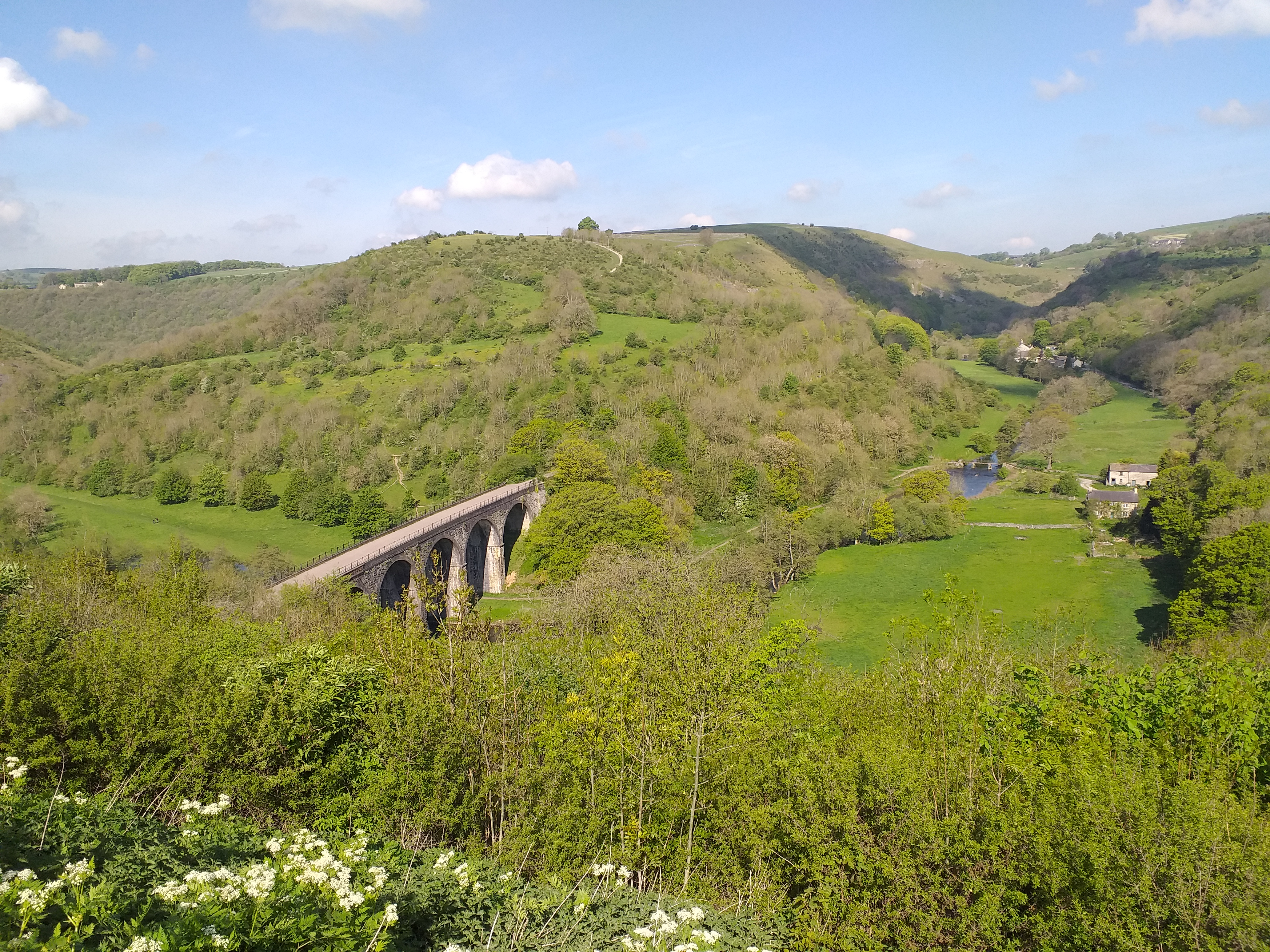 As view over the Monsal Valley with rolling green hills and the stone railway viaduct in the centre, blue skies