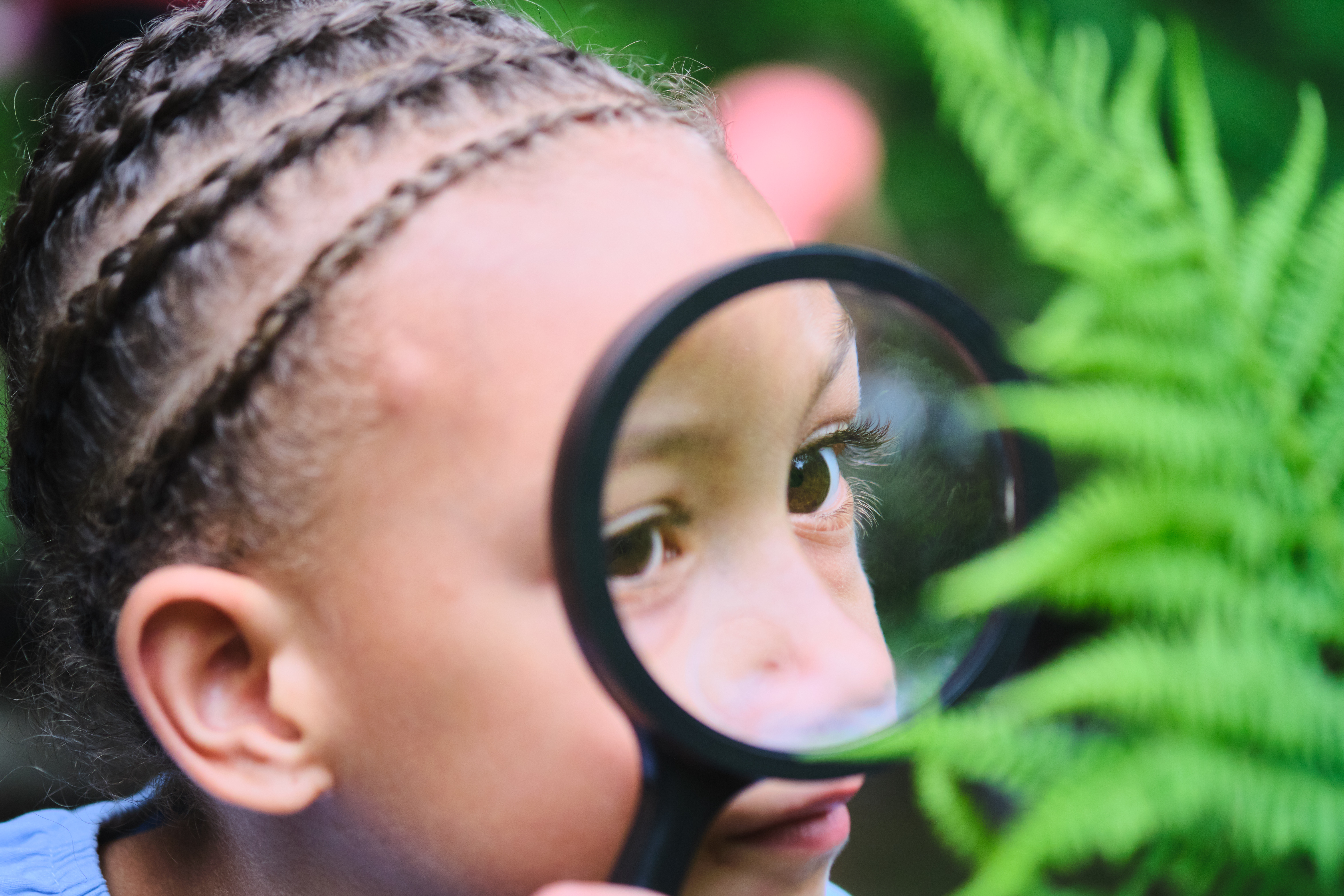 A young child looks through a magnifying glass