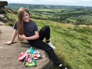 A girls sits on a Peak District edge with a beautiful landscape behind her and a pile of rubbish in front of her