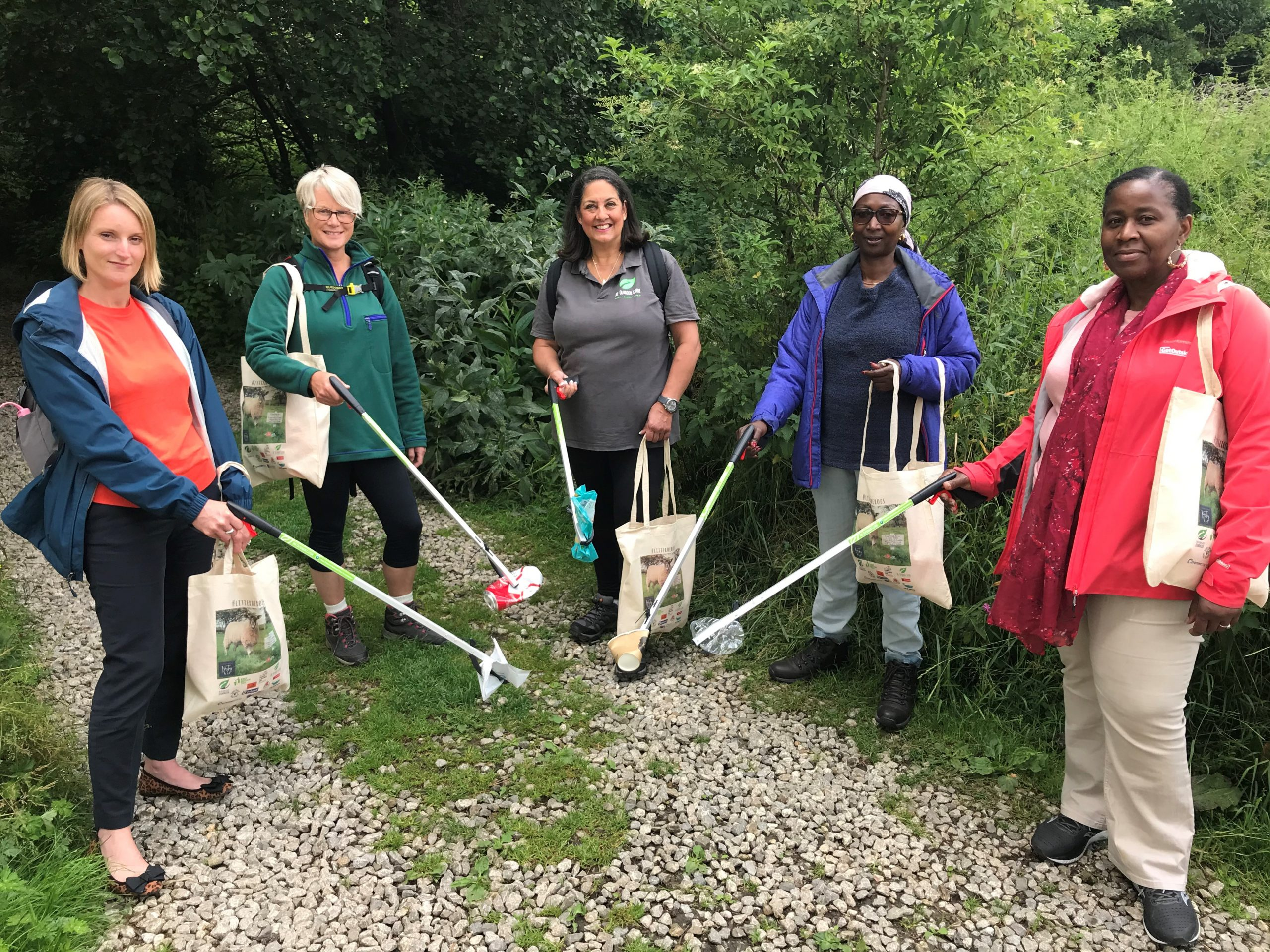 A group of volunteers smile at the camera as they hold up litter pickers with various pieces of rubbish