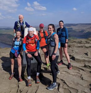 A group of smiling runners stand next to a white Peak District trigg point