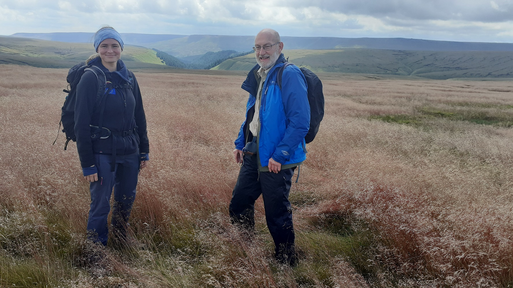 Two figures in blue walking clothes with a view of the Peak District moorland in the background